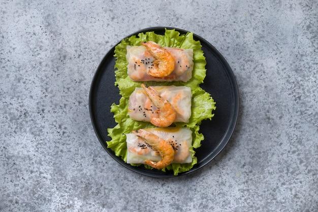Involtini primavera vietnamiti con gamberi in carta di riso su grigio. vista dall'alto cucina asiatica. Foto Premium