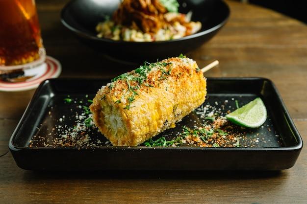 Involtino di mais alla griglia in stile messicano con formaggio e peperoncino in polvere. Foto Premium