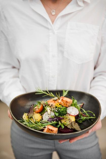 Irriconoscibile donna che tiene il pasto di salmone Foto Gratuite