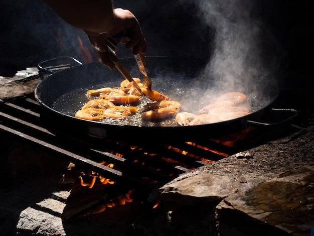 Irriconoscibile fornello che lancia i gamberi che arrostiscono sulla padella con le tenaglie Foto Gratuite