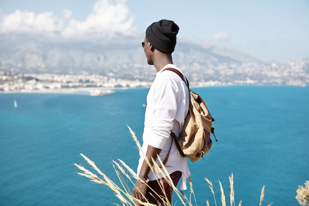 Irriconoscibile giovane turista afroamericano alla moda che gode del bel tempo estivo e del meraviglioso paesaggio marino intorno a lui, mentre in piedi sulla cima della montagna durante un'escursione nell'area tropicale del resort Foto Gratuite