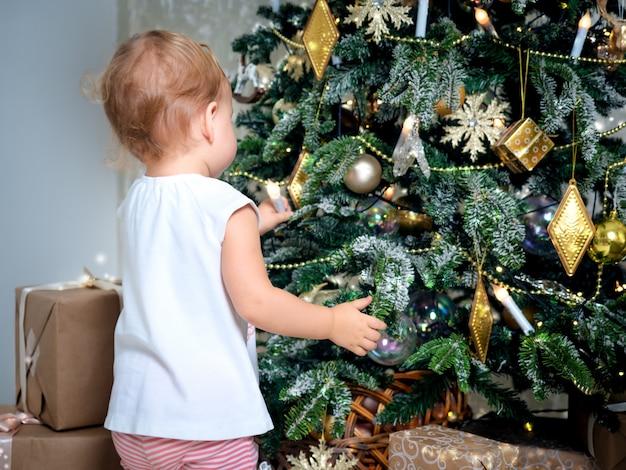 Irriconoscibile piccolo bambino tocca la decorazione dell'albero di natale Foto Premium