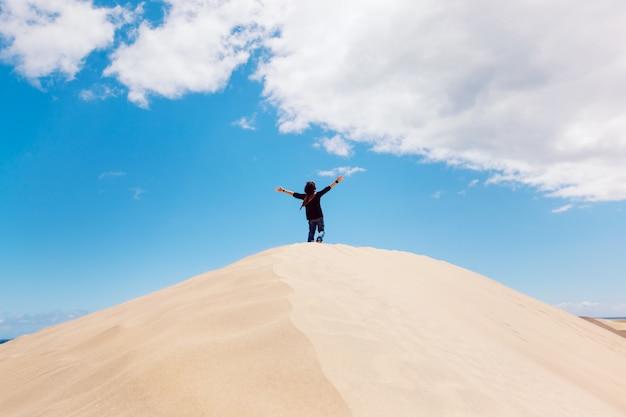 Irriconoscibile uomo con le braccia spalancate sulla cima di una duna del deserto. uomo che gode della libertà. Foto Premium