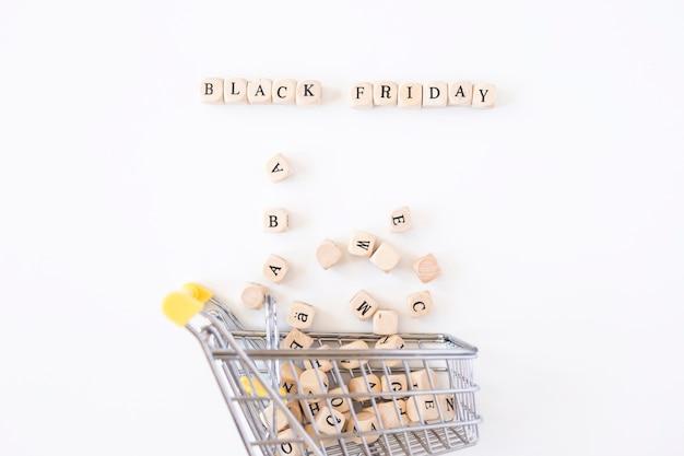 Iscrizione del black friday su cubetti con un piccolo carrello della spesa Foto Gratuite