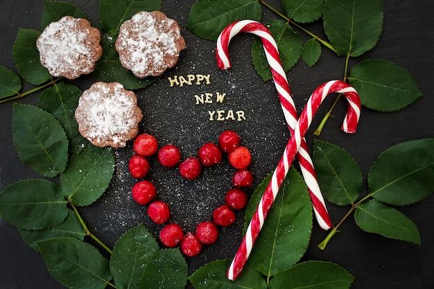 Iscrizione del nuovo anno su un bordo nero con cupcakes e caramelle rosse Foto Premium