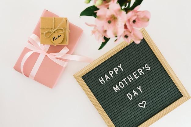 Iscrizione di happy mothers day con fiori e regali Foto Gratuite