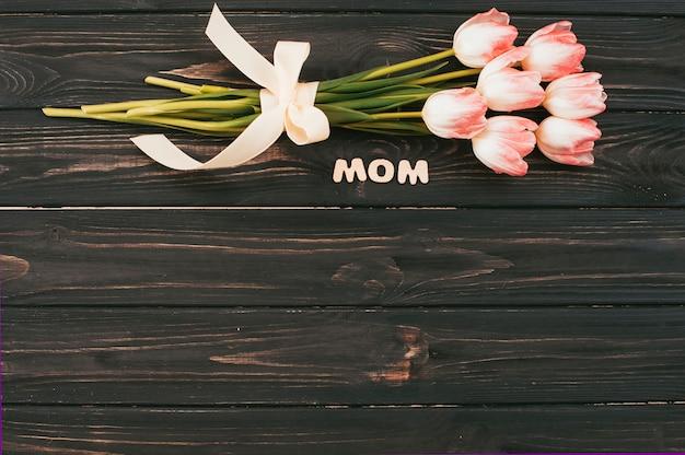Iscrizione di mamma con bouquet di tulipani sul tavolo scuro Foto Gratuite