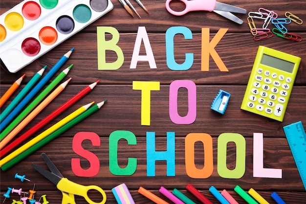 Iscrizione di nuovo a scuola con materiale scolastico su fondo di legno marrone Foto Premium