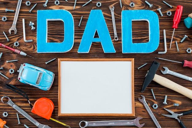 Iscrizione di papà con strumenti e cornice vuota Foto Gratuite