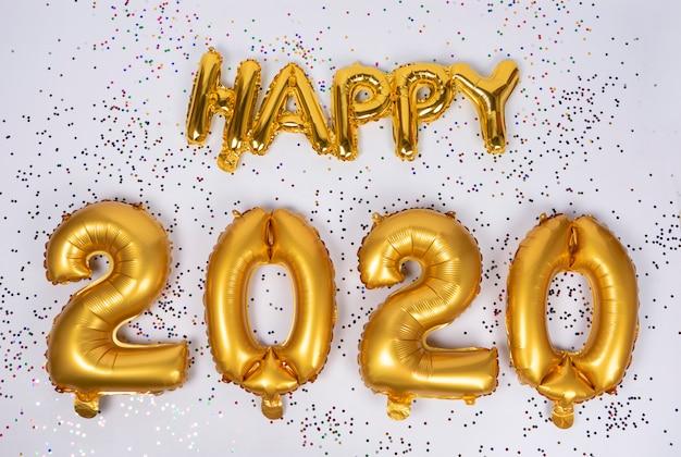Iscrizione felice 2020 di palloncini oro frustrati isolati con coriandoli colorati Foto Premium