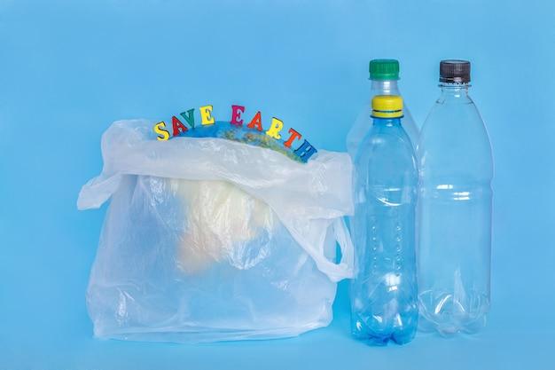 Iscrizione save earth, bottiglie di plastica, terra astratta in sacchetto di polietilene, sfondo blu. Foto Premium