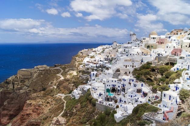Isola di santorini, in grecia. case e chiese tradizionali e famose con cupole blu sulla caldera, sul mar egeo Foto Premium