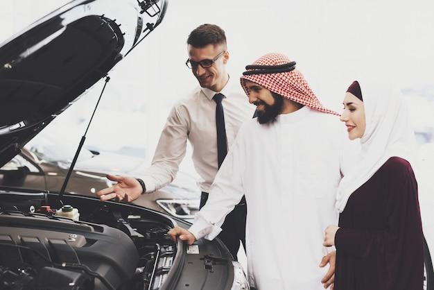 Ispezionando auto sotto cofano qatari family buys car. Foto Premium