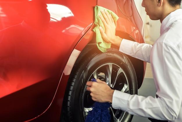 Ispezione e pulizia asiatiche dell'attrezzatura autolavaggio dell'attrezzatura con l'automobile rossa Foto Premium