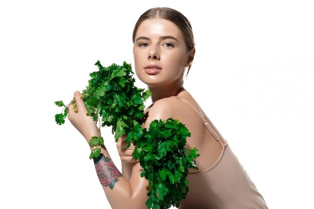 Ispirato. chiuda in su di bella giovane donna con i fogli verdi sul suo fronte sopra bianco. cosmetici e trucco, trattamenti naturali ed ecologici, cura della pelle Foto Gratuite