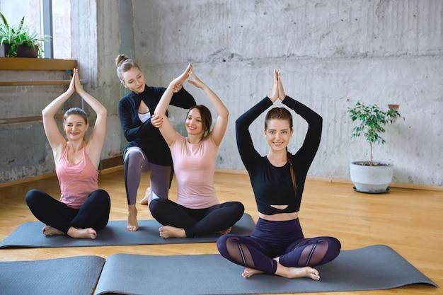 Istruttore che aiuta le donne a praticare la meditazione nella hall. Foto Gratuite