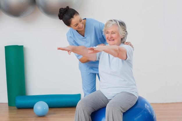 Istruttore che assiste donna senior nell'esercitazione Foto Premium
