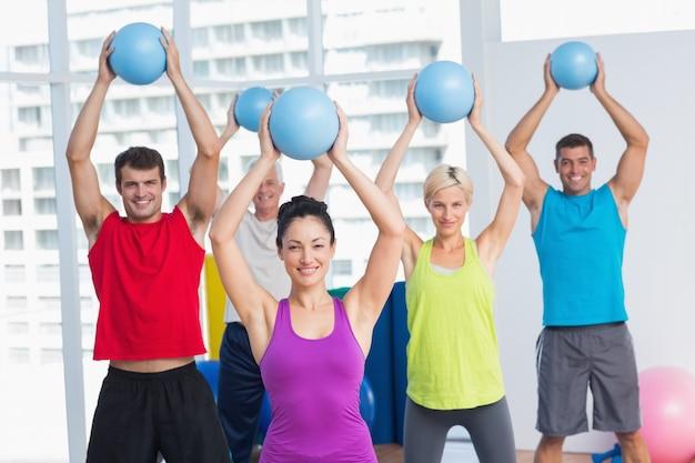 Istruttore con classe che si esercita con le sfere di forma fisica Foto Premium