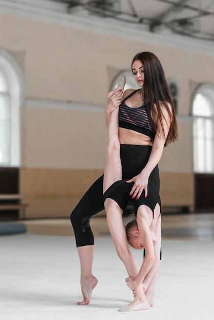Istruttore di danza che assiste la giovane ballerina Foto Gratuite