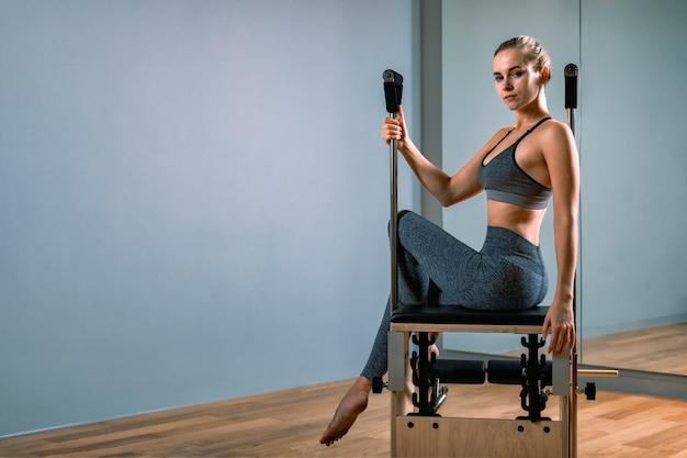 Istruttore femminile che posa per un riformatore in palestra Foto Premium