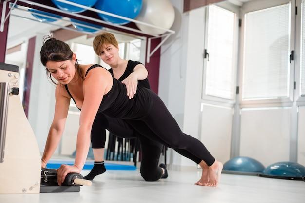 Istruttore personale che controlla giovane donna che si esercita sulla sedia combinata dei pilates di wunda Foto Premium