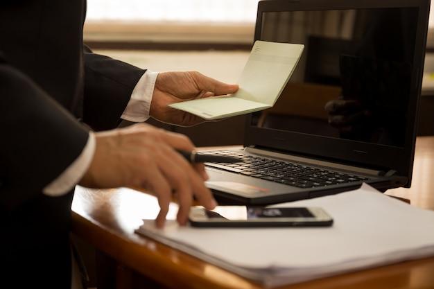 Istruzione finanziaria del libro della tenuta della mano di affari e lavoro con il computer portatile. Foto Premium