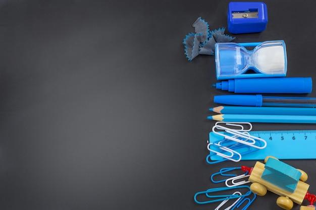 Istruzione o ritorno a scuola. rifornimenti di scuola blu sulla lavagna con copyspace. Foto Premium