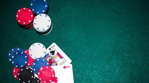 Jack asso e carta asso cuore con fiches del casinò sul tavolo da poker verde Foto Gratuite