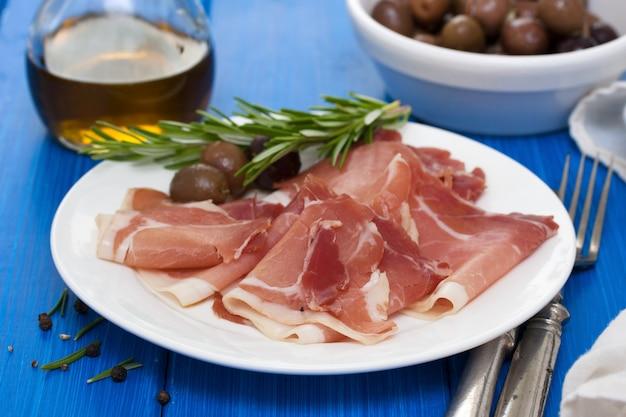 Jamon con olive sul piatto bianco Foto Premium