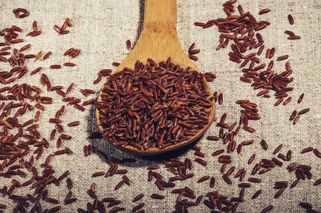 Jasmine brown rice in un cucchiaio di legno sul primo piano naturale del tovagliolo, Foto Premium