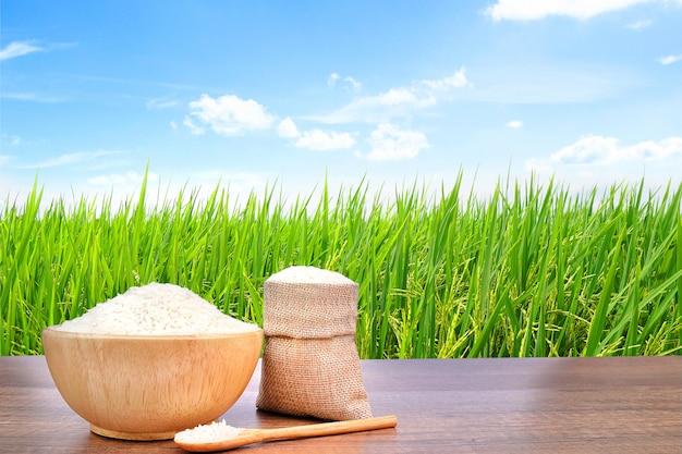 Jasmine rice nella ciotola di legno della tela di sacco e della tela di sacco sulla tavola di legno d'annata con il giacimento verde del riso. Foto Premium