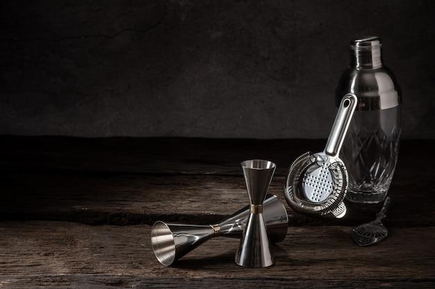 Jigger del filtro dell'agitatore dell'attrezzatura del barista su legno con lo spazio della copia Foto Premium