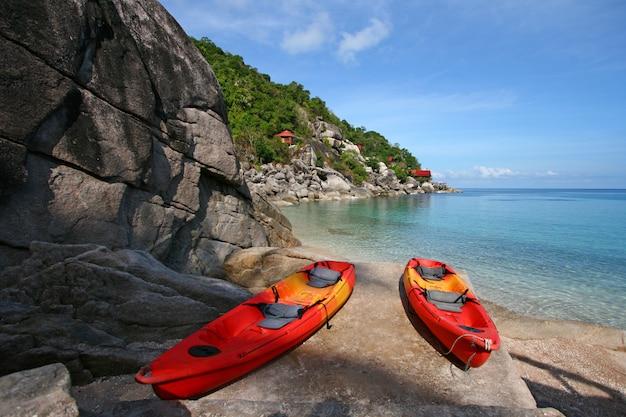 Kayak rosso ormeggiato in spiaggia Foto Premium