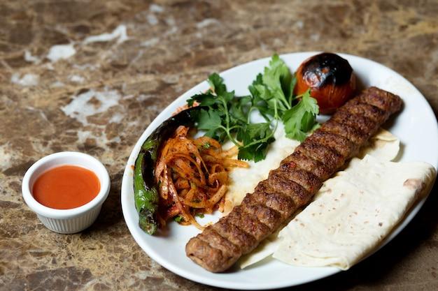 Kebab di adana servito con focaccia, pepe e pomodoro grigliati e cipolla caramellata Foto Gratuite