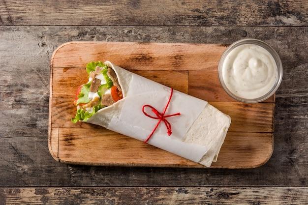 Kebab di doner o panino di shawarma sulla vista di legno del piano d'appoggio Foto Premium