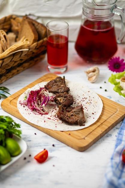 Kebab di manzo con cipolle, sumakh e lavash su un piatto di legno servito con vino e verdure Foto Gratuite