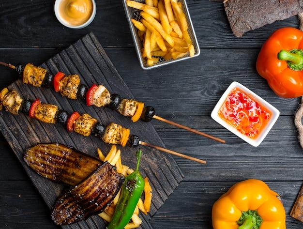 Kebab di pollo con verdure con patatine fritte sul tavolo Foto Gratuite