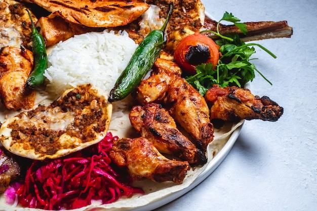 Kebab di pollo di vista laterale con il cavolo ed il riso marinati pomodoro caldo caldo del peperone verde sulla pita Foto Gratuite