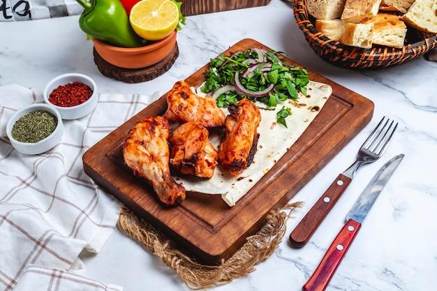 Kebab di pollo di vista laterale sul pane della pita con le erbe e le cipolle su una lavagna Foto Gratuite