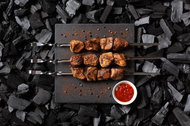 Kebab su spiedini. tre porzioni di carne alla griglia su un piatto di pietra. carbone di legna vista dall'alto. Foto Premium