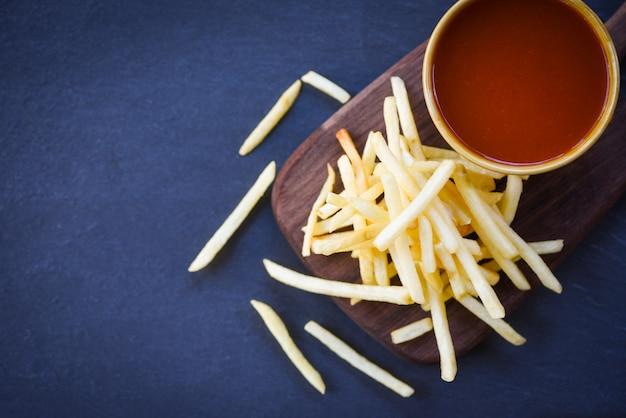 Ketchup di patatine fritte in tavola di legno con sfondo nero - gustose patatine fritte per cibo o snack deliziosi ingredienti fatti in casa italiani Foto Premium