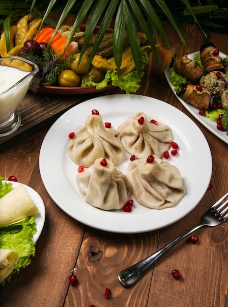 Khinkali georgiano tradizionale dell'alimento sul piatto bianco con il melograno, forcella, erbe Foto Gratuite