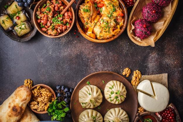 Khinkali, phali, chakhokhbili, lobio, formaggio, involtini di melanzane, tavolo scuro. Foto Premium
