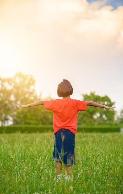 Kid in piedi e allungare le braccia o estendere le braccia nei campi di erba Foto Premium