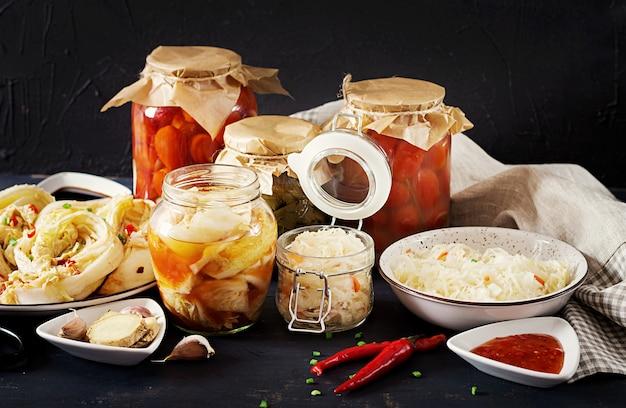 Kimchi di cavolo, pomodori marinati, vasetti di crauti in agrodolce sul tavolo della cucina rustica. Foto Gratuite