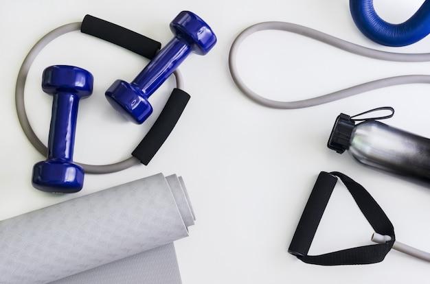 Kit sportivo: manubri, espansore, tappetino yoga, borraccia. Foto Premium