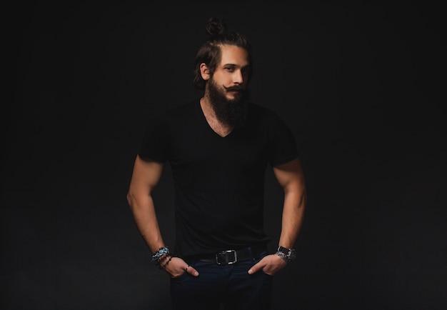 L uomo con la barba e capelli lunghi raccolti in una coda