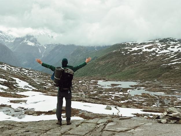 L'uomo con una zainetta ama il paesaggio montano splendido Foto Gratuite