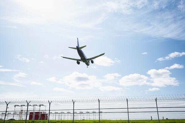 L'aereo atterra sulla pista dell'aeroporto contro un cielo blu brillante. Foto Premium