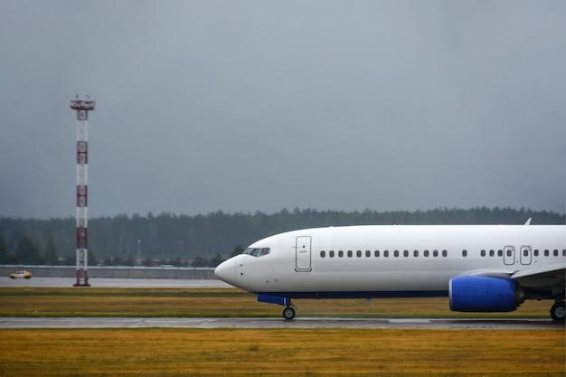 L'aereo di linea del passeggero è atterrato sulla pista dell'aeroporto in caso di maltempo con la pioggia Foto Premium